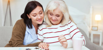 caregiver and elderly woman doing jigsaw puzzle