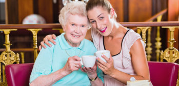caregiver and elderly woman having a tea