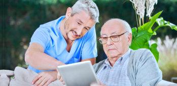 caregiver assisting elderly man in using tablet