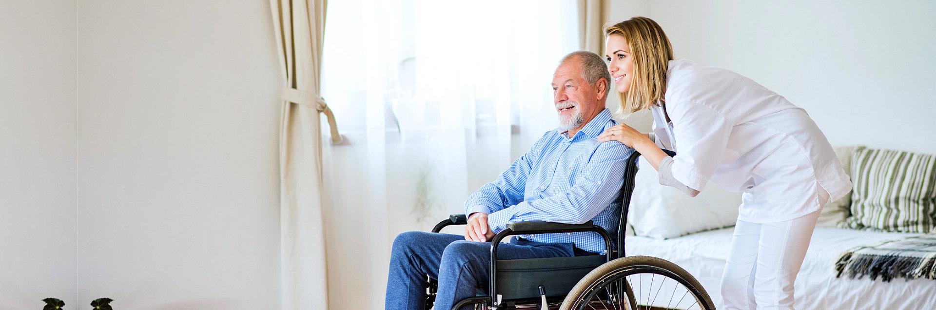 caregiver and elderly man in a wheelchair