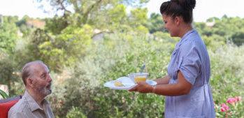 caregiver serving meal for elderly man