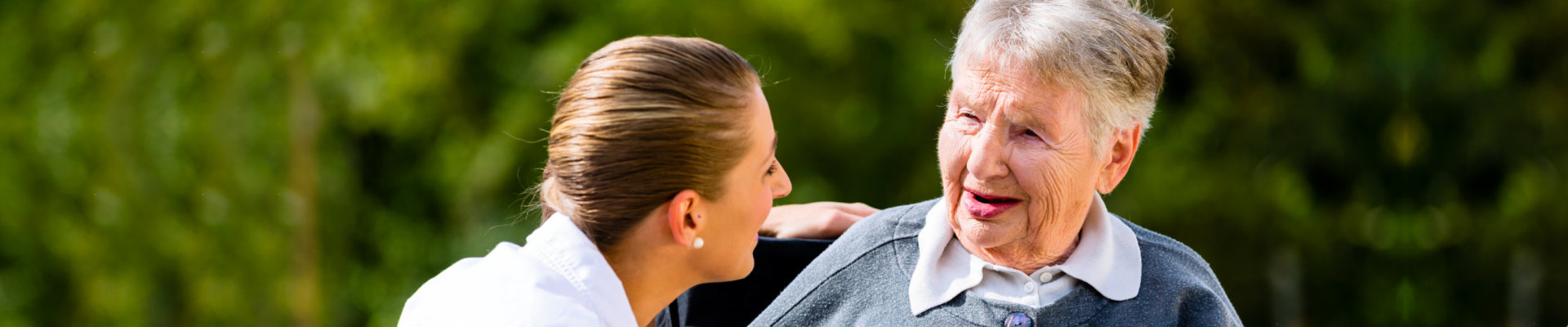 caregiver and elderly lady smiling at each other
